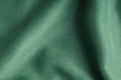 Green background cloth wavy folds textile texture Royalty Free Stock Photo