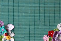 Green background with crochet flowers. Green background with crochet colorfull flowers and bird Stock Images