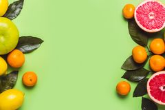 Green background with different citrus fruits. Healthy food concept royalty free stock photography