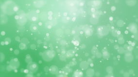 Green background with light bokeh particles. Festive green bokeh background with flickering light particles imitating underwater bubbles stock video