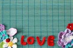 Green background  with red crocheted. Superscription of love and flowers Royalty Free Stock Photography