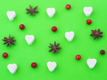 Green background with sugar heart, anise stars and cranberries. Top view Stock Image