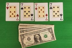 Four sevens win money in casino. Green background table casino corner four sevens bet gambling gamble game cards cash chance luck money play win winner poker royalty free stock image