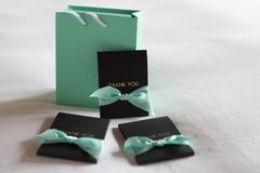 Green bag with black thank you card and green bow on white bed. Green bag with thank you card and green bow on white bed Stock Photos