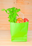 Green bag with healthy food on wooden background Stock Image