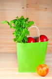 Green bag with healthy food on the wooden background Stock Photography