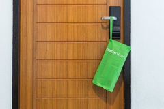 Green bag with newspaper hang on the door in hotel Royalty Free Stock Photography