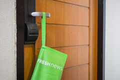 Green bag with newspaper hang on the door in hotel stock photography