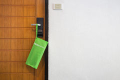 Green bag with newspaper hang on the door in hotel Stock Image