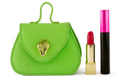 Green bag, red lipstick, black mascara. Small green bag with red lipstick and mascara on the side Royalty Free Stock Photography