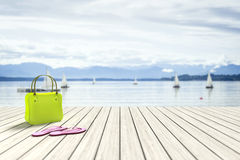 Green bag on a wooden jetty with sailing boats in the background. 3d rendering of a green bag on a wooden jetty with sailing boats in the background stock illustration