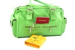 Green bag and yellow wallet. View at green handbag with passport in a pocket and yellow wallet stock photo