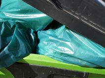 Green bags of rubbish in a bin Stock Photos