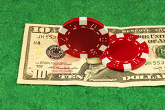 On the green baize is ten dollars and casino chips Royalty Free Stock Photo