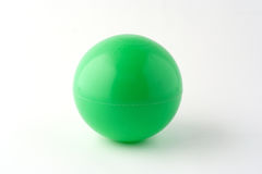 Green ball. A green plastic little ball on white table Royalty Free Stock Image