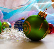 Green ball on Christmas tree. Beautiful festive greeting card with colorful balloons and décor Royalty Free Stock Image