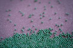 Green ball crystal sugar sprinkle dots, on glitter pink background. Green ball crystal sugar sprinkle dots, on glitter pink background, decoration for royalty free stock photo