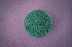 Green ball crystal sugar sprinkle dots, on glitter pink background. Green ball crystal sugar sprinkle dots, on glitter pink background, decoration for royalty free stock photography