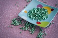 Green ball crystal sugar sprinkle dots, on glitter pink background. Green ball crystal sugar sprinkle dots, on glitter pink background, decoration for stock image