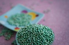 Green ball crystal sugar sprinkle dots, on glitter pink background. Green ball crystal sugar sprinkle dots, on glitter pink background, decoration for stock photos