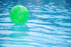 Green ball floating in swimming pool. Green ball floating in deep blue swimming pool Royalty Free Stock Image