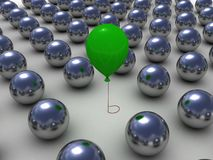 Green balloon among the metallic balls Stock Image