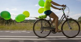 Woman on a Bike with balloons. Green balloons attached to the bicycle Stock Photos