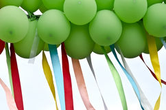 Green balloons with developing colorful ribbons Stock Photography
