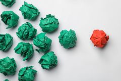 Green balls of crumpled paper following red one on white background, top view. Leadership concept stock photo