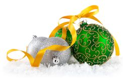 Green balls in snow with gold bow Stock Photo