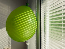 Green baloon. On the window inside, with the sun shining through the window Royalty Free Stock Photo
