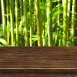 Green bamboo grove background with wooden table Stock Photo