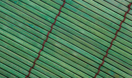 Green bamboo placemat. Rough textured green bamboo placemat with brown stitching Royalty Free Stock Image