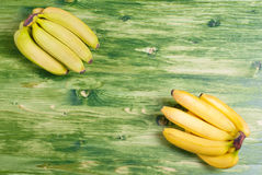 Green banana in the upper left corner of the yellow banana in th Stock Image