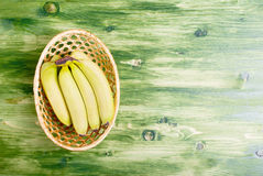 Green banana in a wicker basket on a green chalkboard on the rig Royalty Free Stock Image