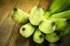 Green banana on wooden table Royalty Free Stock Images