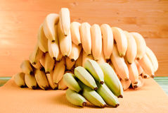 Green bananas and a lot of yellow bananas on the green board on Royalty Free Stock Images