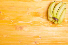 Green bananas in the upper right corner of the yellow board on t Royalty Free Stock Photography