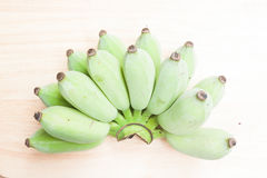Green bananas on wood background Royalty Free Stock Images