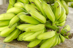 Green bananas on a wooden table. Royalty Free Stock Image