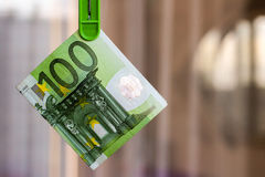 Green banknote 100 euro in green clothes peg. Green banknote 100 euro in a green clothes peg Royalty Free Stock Photography