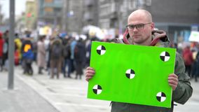 Green banner in hands protester. Sad man with a poster in hands. 20s caucasian boy. Crowd people in the background on street. A men agitates by propaganda with stock footage