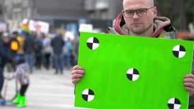 Green banner in hands protester. Sad man with a poster in hands. 20s caucasion boy. Crowd people in the background on street. People protesting in Moscow stock video footage