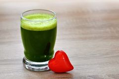 Green barley juice drink in glass and red heart on wood background. Detox superfood. The concept of healthy eating Stock Images