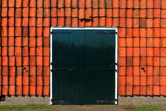 Green barn doors with red roof tiles Stock Photography