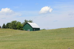 Green barn on hill. Top. Blue sky with beautiful clouds Stock Photo