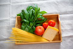 Green basil, chunk of parmesan cheese, raw cappellini and tomatoes Royalty Free Stock Images