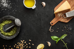 Green basil pesto - italian recipe ingredients on black chalkboard Stock Images