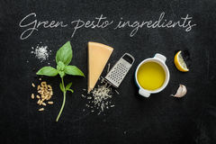 Green basil pesto - italian recipe ingredients on black chalkboard. Background from above. Parmesan cheese, basil leaves, pine nuts, lemon, olive oil, garlic royalty free stock image