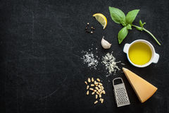 Green basil pesto - italian recipe ingredients on black chalkboard Royalty Free Stock Images